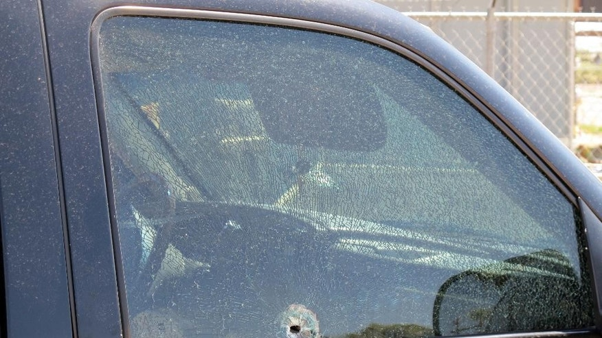 This Saturday, Aug. 29, 2015 photo provided by The Arizona Department of Public Safety shows a SUV window shattered by a gun shot in Phoenix. Authorities say shots were fired at several vehicles on Interstate 10 in Phoenix over the weekend, with bullets striking three vehicles and injuring one person. (The Arizona Department of Public Safety via AP)