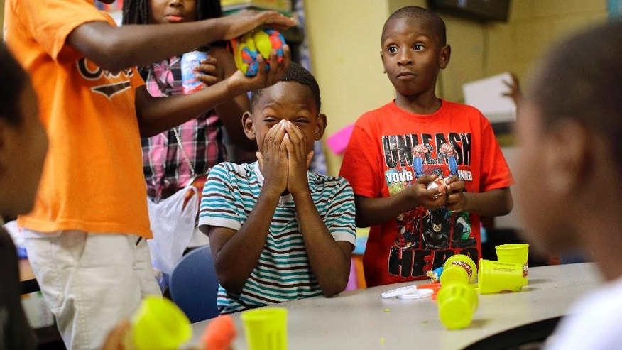 In this Aug. 19, 2015, photo, children play with Play-Doh at Kids Safe Zone community center in Baltimore. The clubhouse, which occupies an abandoned laundromat, opened in June in response to unrest that ripped through the neighborhood's streets and marked the beginning of the most violent summer the city has seen in more than four decades. (AP Photo/Patrick Semansky)