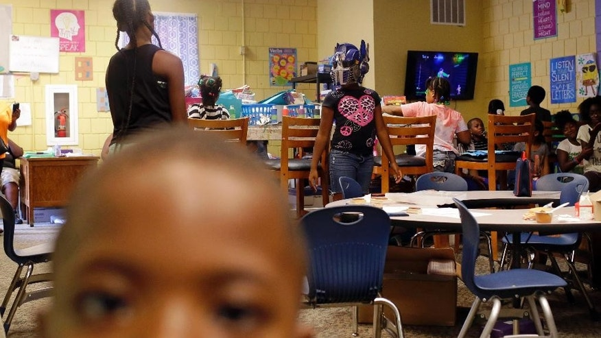 In this Aug. 19, 2015, photo, children play at Kids Safe Zone community center in Baltimore. The clubhouse, which occupies an abandoned laundromat, opened in June in response to unrest that ripped through the neighborhood's streets and marked the beginning of the most violent summer the city has seen in more than four decades. (AP Photo/Patrick Semansky)