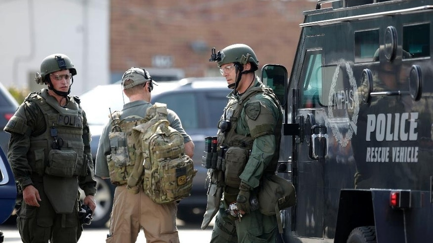 Police officers gather before heading out for a manhunt after an officer was shot in Fox Lake, Ill., on Tuesday, Sept. 1, 2015.  Lake County Major Crimes Task Force Cmdr. George Filenko says an officer was shot Tuesday morning in Fox Lake, 55 miles north of Chicago.  (Stacey Wescott/Chicago Tribune via AP) MANDATORY CREDIT CHICAGO TRIBUNE; CHICAGO SUN-TIMES OUT; DAILY HERALD OUT; NORTHWEST HERALD OUT; THE HERALD-NEWS OUT; DAILY CHRONICLE OUT; THE TIMES OF NORTHWEST INDIANA OUT; TV OUT; MAGS OUT; NO SALES