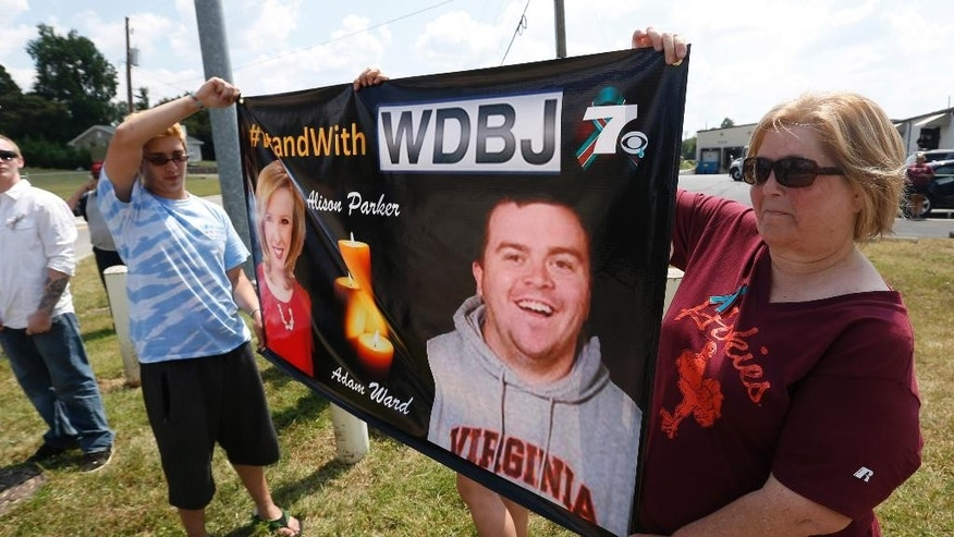 Local residents Hunter Cregger, left, and his mother Sandra Cregger, show their support for WDBJ-TV cameraman Adam Ward at the Blue Ridge Memorial Garden cemetery in Roanoke, Va., Tuesday, Sept. 1, 2015. Ward and WDBJ-TV morning reporter Alison Parker were fatally shot by a former co-worker on live television during an interview on Aug. 26. (AP Photo/Steve Helber)