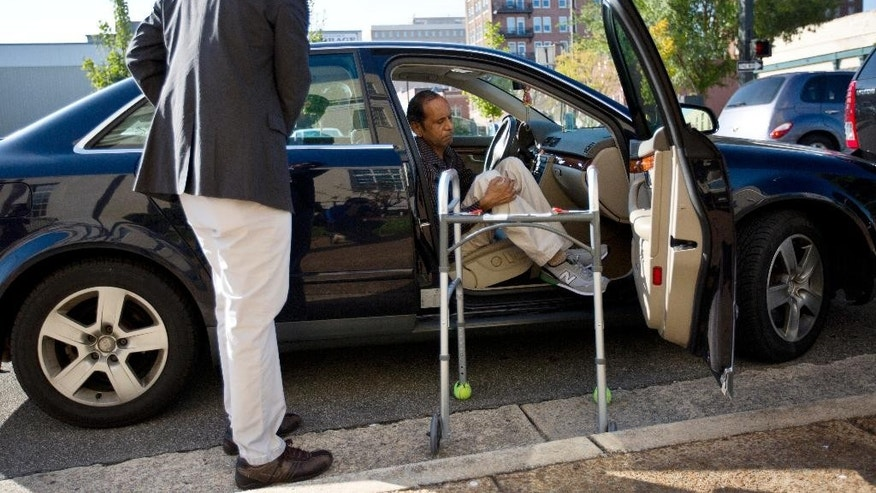 Chirag Patel helps his father, Sureshbhai Patel out of the car as they arrive outside the federal courthouse before start of a trial against Madison, Ala., police officer Eric Sloan Parker, Tuesday, Sept. 1, 2015, in Huntsville, Ala. Patel, who was visiting relatives from his native India in February, was walking in his son's neighborhood when police responding to a call about a suspicious person stopped to question him. A police video captured an officer slamming the man to the ground, partially paralyzing him. (AP Photo/Brynn Anderson)