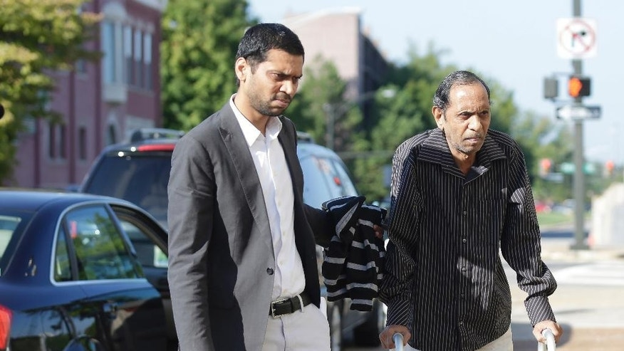Chirag Patel helps his father, Sureshbhai Patel as they arrive outside the federal courthouse before start of a trial against Madison, Ala., police officer Eric Sloan Parker, Tuesday, Sept. 1, 2015, in Huntsville, Ala. Patel, who was visiting relatives from his native India in February, was walking in his son's neighborhood when police responding to a call about a suspicious person stopped to question him. A police video captured an officer slamming the man to the ground, partially paralyzing him. (AP Photo/Brynn Anderson)