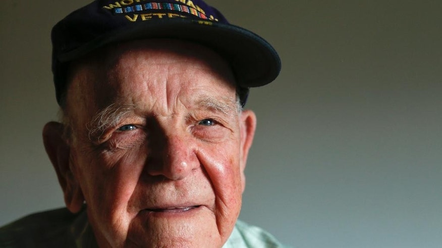 In this Aug. 12, 2015 photo, World War II veteran Stephen Dennis poses in Mechanicville, N.Y. Dennis enlisted in the Navy soon after the Japanese attacked Pearl Harbor. Less than a year later, he survived one of the Pacific's fiercest naval battles. On the day Japan formally surrendered to end WWII, the young sailor from upstate New York was transmitting the news to the world that the bloodiest conflict in history was officially over. (AP Photo/Mike Groll)