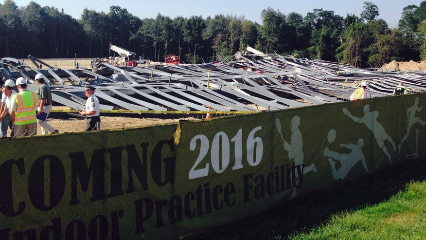 Sept. 1, 2015: People walk past bent steel at a construction site where an athletic practice facility on the Bryant University campus collapsed.
