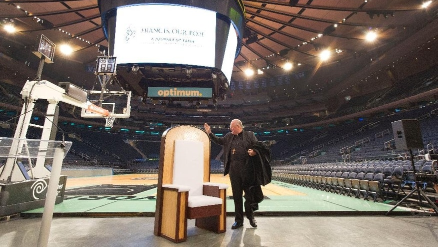 Cardinal Timothy Dolan, the Archbishop of New York, unveils the Pope's chair during a media event at New York's Madison Square Garden, Wednesday, Sept. 2, 2015. The simple wooden chair has been built for Pope Francis when he celebrates Mass at the sports and entertainment arena on Friday, Sept. 25. (AP Photo/Mark Lennihan)