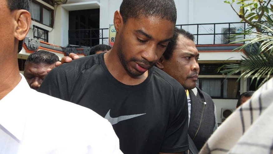 Former Austin,Texas, police officer VonTrey Jamal Clark, center, is escorted by Indonesian police officers during his extradition in connection with a murder case at the regional police headquarters in Bali, Indonesia, Wednesday, Sept. 2, 2015. Clark, 32, sought in the murder of his pregnant girlfriend was extradited Wednesday from Indonesia to the United States. Clark was handed over to 13 agents of the FBI and was flown from Ngurah Rai airport in Denpasar, the provincial capital of Bali resort island, to Texas on a specially chartered plane from the bureau. (AP Photo/Firdia Lisnawati)