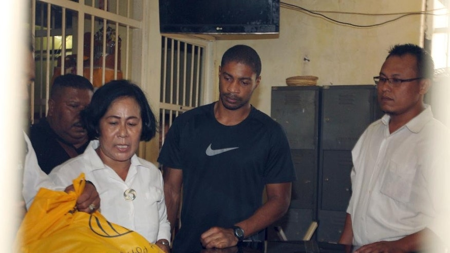 Former Austin,Texas, police officer VonTrey Jamal Clark, center, is checked by Indonesian police officers in a cell before his extradition in connection with a murder case at the regional police headquarters in Bali, Indonesia, Wednesday, Sept. 2, 2015. Clark, 32, sought in the murder of his pregnant girlfriend was extradited Wednesday from Indonesia to the United States. Clark was handed over to 13 agents of the FBI and was flown from Ngurah Rai airport in Denpasar, the provincial capital of Bali resort island, to Texas on a specially chartered plane from the bureau. (AP Photo/Firdia Lisnawati)