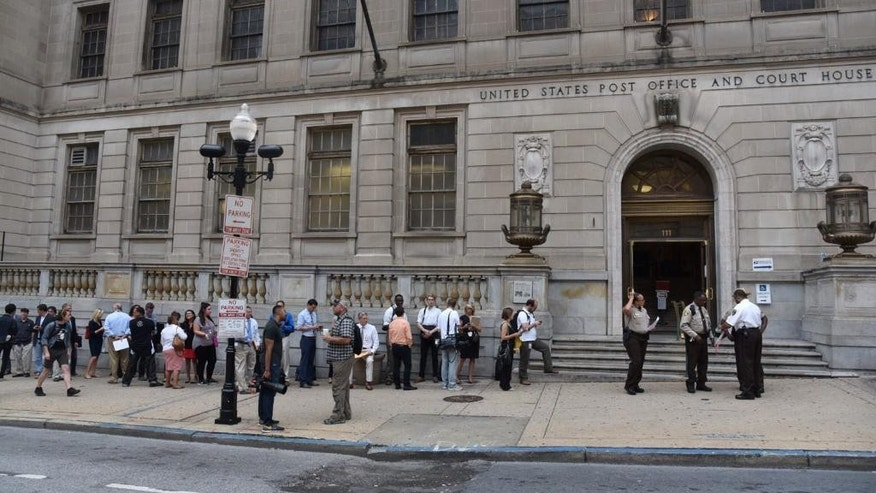 "Members of the media stand in line to enter the Baltimore Circuit Court, as the first court hearing was set to begin in the case of six police officers criminally charged in the death of Freddie Gray, on Wednesday, Sept. 2, 2015 in Baltimore.  Six police officers face charges that range from second-degree assault, a misdemeanor, to second-degree ""depraved-heart"" murder.   (Kim Hairston/The Baltimore Sun via AP)  WASHINGTON EXAMINER OUT; MANDATORY CREDIT"