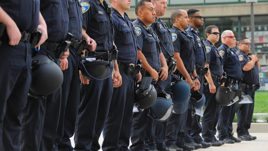 "Baltimore police officers form a line at the Inner Harbor on Pratt Street as protestors gathered, blocking traffic, Wednesday, Sept. 2, 2015 in Baltimore, as the first court hearing was set to begin in the case of six police officers criminally charged in the death of Freddie Gray.  Six police officers face charges that range from second-degree assault, a misdemeanor, to second-degree ""depraved-heart"" murder.   (Lloyd Fox/The Baltimore Sun via AP)  WASHINGTON EXAMINER OUT; MANDATORY CREDIT"