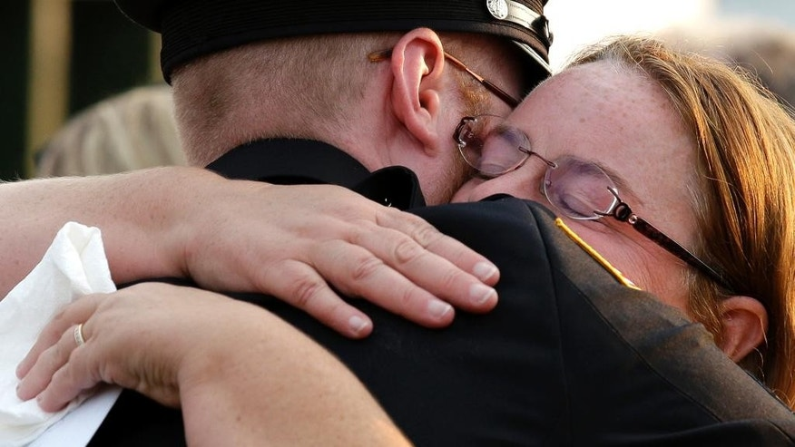 Fox Lake Police Lt. Charles Joseph Gliniewicz's wife Mel, right, hugs a mourner during a vigil at Lakefront Park to honor him, Wednesday, Sept. 2, 2015, in Fox Lake, Ill. Gliniewicz was shot and killed Tuesday while pursuing a group of suspicious men. Authorities broadened the hunt Wednesday for the suspects wanted in the fatal shooting. (AP Photo/Nam Y. Huh)