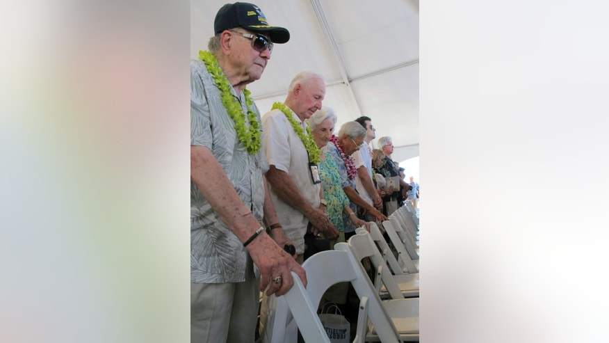 Veterans and their families bow their heads during a ceremony marking the 70th anniversary of the end of World War II, Wednesday, Sept. 2, 2015 in Pearl Harbor, Hawaii. The veterans gathered on board the decomissioned battleship Missouri, the same ship Japanese Foreign Minister Mamoru Shigemitsu and Army Gen. Yoshijiro Umezu boarded in Tokyo Bay on Sept. 2, 1945 to sign documents to formally surrender. (AP Photo/Audrey McAvoy)