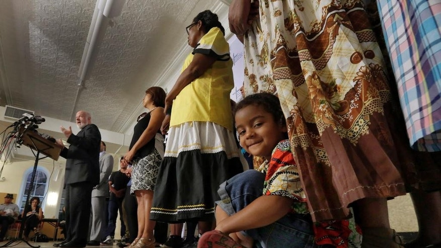 CORRECTS SPELLING OF FIRST NAME TO KINGSON, KINGSTON - Kingson Noe Suazo David, 4, right, of Garifuna, a group of indigenous Hondurans, listens as Monsignor Kevin Sullivan, left, introduces people at Saint Cecilia's Parish, Thursday, Sept. 3, 2015, who will be blessed by Pope Francis, during his visit to New York. (AP Photo/Richard Drew)