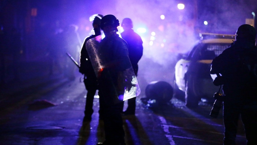 Nov. 25, 2014: Police officers watch protesters as smoke fills the streets in Ferguson, Mo. after a grand jury's decision in the fatal shooting of Michael Brown.
