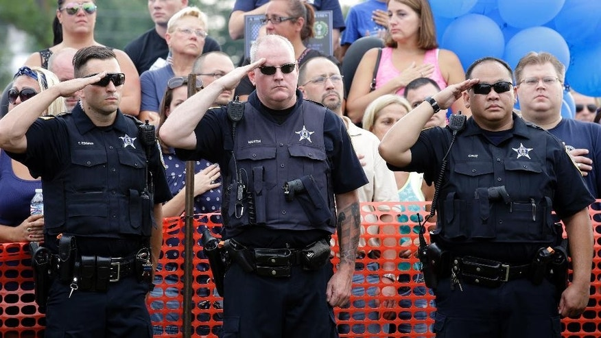 Officers salute as the family of slain Fox Lake police officer Lt. Joe Gliniewicz during a vigil at Lakefront Park to honor him, Wednesday, Sept. 2, 2015, in Fox Lake, Ill. Gliniewicz was shot and killed Tuesday while pursuing a group of suspicious men. Authorities broadened the hunt Wednesday for the suspects wanted in the fatal shooting. (AP Photo/Nam Y. Huh)