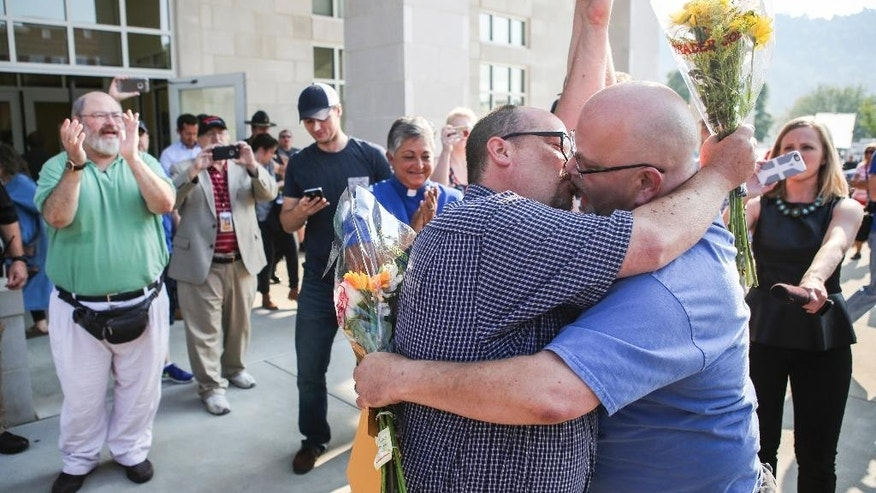 "Michael Long, left, and Timothy Long kiss outside the Rowan County Judicial Center in Morehead, Ky., Friday, Sept. 4, 2015, raising their fist clinched high in to the air after being the second couple to receive a marriage license. Gay couples walked out of the Kentucky courthouse with marriage licenses Friday, a day after the county's defiant clerk, Kim Davis, was taken to jail for refusing to license same-sex marriages, citing ""God's authority."" (Alton Strupp/The Courier-Journal via AP) NO SALES; MAGS OUT; NO ARCHIVE; MANDATORY CREDIT"
