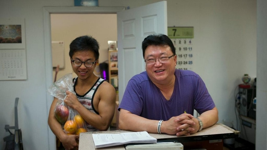 In this Tuesday, July 14, 2015 photo, pastor Young Ho Han, right, shares a light moment with recovering drug addict Steve Yoo at Nanoom Christian Fellowship, a drug rehab for Korean Americans, in Los Angeles. In a blue-and-white painted church on the outskirts of Los Angeles' Koreatown, pastor Han is trying to lift the veil on a problem silently scourging his community: Drug abuse among young Korean Americans. (AP Photo/Jae C. Hong)