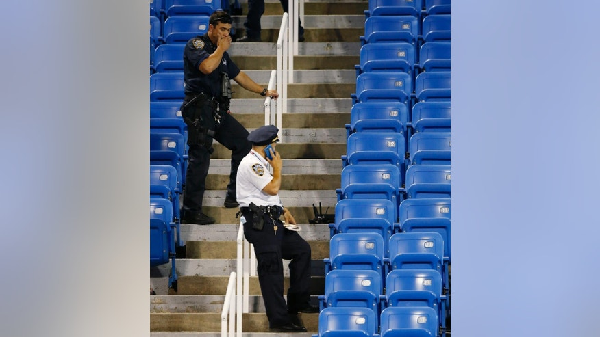 Police officers investigate after a drone buzzed a match between Flavia Pennetta, of Italy, and Monica Niculescu, of Romania, at the U.S. Open tennis tournament in New York, Thursday, Sept. 3, 2015. (AP Photo/Kathy Willens)