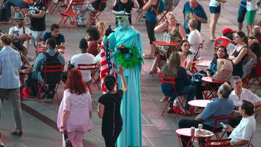 A costumed character dressed as the Statue of Liberty interacts with visitors in Times Square Wednesday, Sept. 2, 2015, in New York. Concerned that Times Square is becoming less wholesome, the NYPD is assigning plainclothes officers to discourage aggressive panhandling in a tourist attraction that long ago rid itself of prostitutes and junkies. (AP Photo/Craig Ruttle)