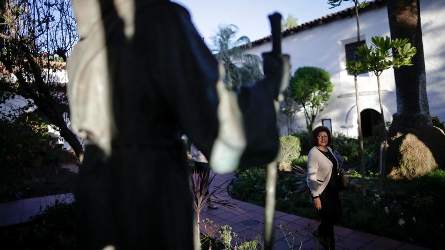 FILE - In this Jan. 27, 2015 file photo, a woman passes a statue of Franciscan missionary Junipero Serra at the Mission San Diego de Acala in San Diego. Pope Francis' apology for the Roman Catholic Church's crimes against indigenous peoples has not softened opposition among some California Native Americans to his decision to canonize 18th-century Franciscan missionary Junipero Serra, extolled by the Vatican as a great evangelizer, but denounced by some tribal officials as a destroyer of Native culture. (AP Photo/Gregory Bull, File)