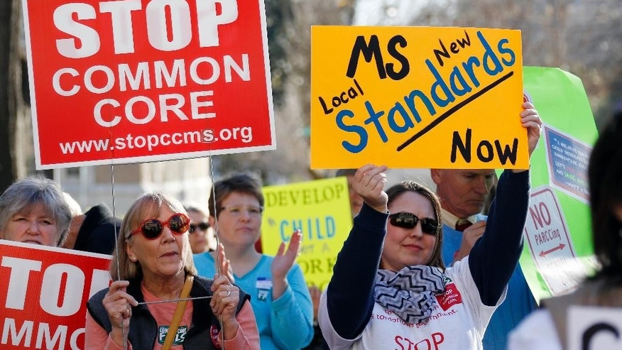 FILE - In this Jan. 6, 2015 file photo, Common Core opponents wave signs and cheer at a rally opposing Mississippi's continued use of the Common Core academic standards on the steps of the Capitol in Jackson, Miss.   Results for some of the states that participated in Common Core-aligned testing for the first time this spring are out, with overall scores higher than expected though still below what many parents may be accustomed to seeing.   (AP Photo/Rogelio V. Solis,File)