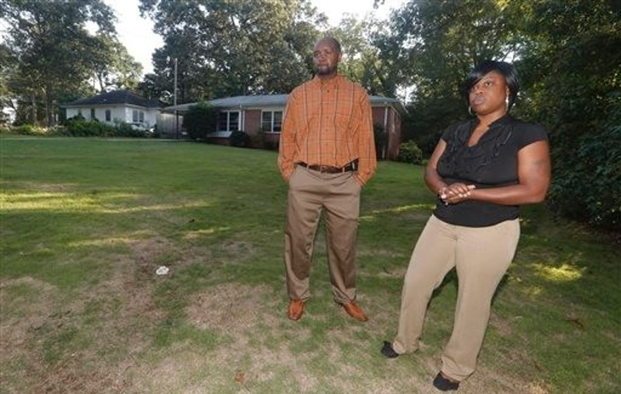 In this photo taken Thursday,  Aug. 20, 2015, Gregory Bonds and his wife Sophia stand in front of their former home in Atlanta.  (AP Photo/John Bazemore)