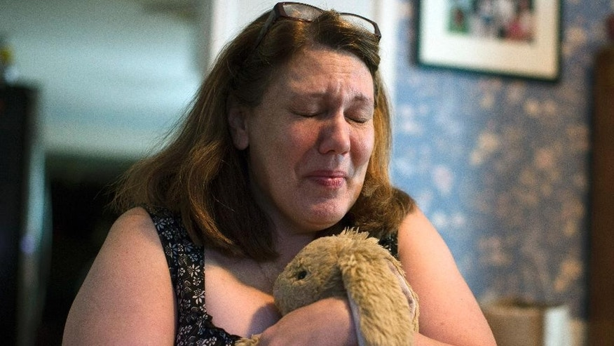 In this Wednesday, Sept. 2, 2015, photo, Dorothy McIntosh Shuemake, mother of Alison Shuemake, cries as she clutches her daughter's toy stuffed rabbit during an interview at her home, in Middletown, Ohio. Alison Shuemake, 18, died Aug. 26, after a suspected heroin overdose when she and her partner were found unresponsive at their home and needles were present nearby. (AP Photo/John Minchillo)