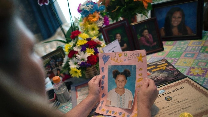 In this Wednesday, Sept. 2, 2015, photo, Dorothy McIntosh Shuemake, mother of Alison Shuemake, holds a picture of her daughter during an interview at her home, in Middletown, Ohio. Alison Shuemake, 18, died Aug. 26, after a suspected heroin overdose, when she and her partner were found unresponsive at their home and needles were present nearby. (AP Photo/John Minchillo)