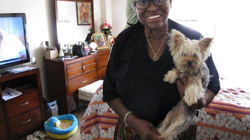 In this Tuesday, Aug. 25, 2015 photo, Bonnie Jean Cook holds her therapy dog, Bella, in her apartment in East Hartford, Conn. Cook, 68, is adjusting to modern life, including her iPhone and Facebook, after serving 27 years in prison for murder. Cook, convicted of murder in the shooting death of a pregnant woman in 1986 when her name was Bonnie Foreshaw, won early release in 2013. (AP Photo/Dave Collins)
