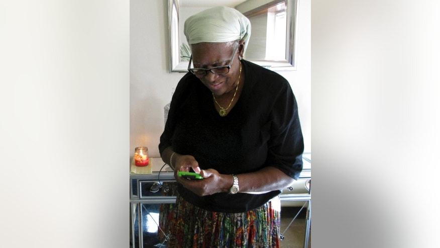 In this Tuesday, Aug. 25, 2015 photo, Bonnie Cook uses her iPhone in her apartment in East Hartford, Conn. Cook, 68, is adjusting to modern life, including her iPhone and Facebook, after serving 27 years in prison for murder. Cook, convicted of murder in the shooting death of a pregnant woman in 1986 when her name was Bonnie Foreshaw, won early release in 2013. (AP Photo/Dave Collins)
