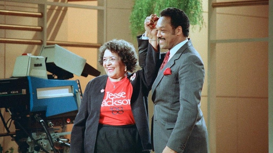 FILE - Democratic presidential hopeful Jesse Jackson clasps hands with his mother, Helen Jackson, during taping of the Phil Donahue show in New York. Jackson told The Associated Press his mother died Monday, Sept. 7, 2015 in her longtime hometown of Greenville, S.C. He says she had been in failing health for some time. She was 92. (AP Photo/Barry Thumma, file)