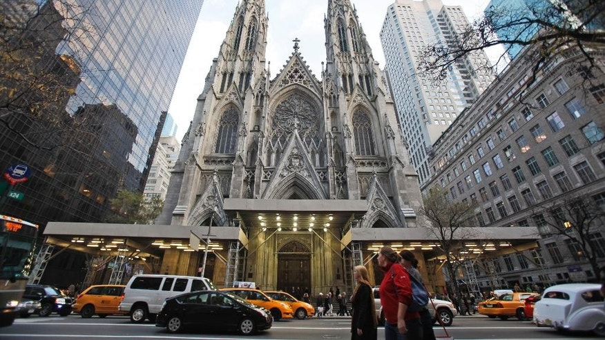 FILE - In this Nov. 20, 2010 photo, visitors to New York's Fifth Avenue walk past St. Patrick's Cathedral. The 2,200-seat white marble cathedral opened in 1879. In September 2015, the restoration project at the cathedral is coming to an end, in time for a visit from Pope Francis. (AP Photo/Mary Altaffer, File)