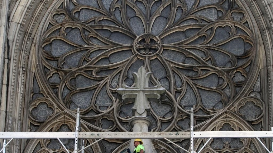 FILE - In this Tuesday, July 3, 2012 file photo, a construction worker walks on scaffolding past the great rose window during renovations at St. Patrick's Cathedral in New York. St. Patrick's held its first Mass in 1879 and was declared a national landmark in 1976. A three-year restoration project at the cathedral is coming to an end, just in time for a late September, 2015 visit from Pope Francis. (AP Photo/Mary Altaffer, File)