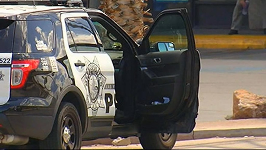 In this image taken from KTNV video, police officers investigate the scene where a police officer was shot while stopped at a traffic light in Las Vegas, NV. Sunday, Sept. 6, 2015. Metro Police Sgt. John Sheahan told the Las Vegas Sun that two officers were on their way to respond to a call about a disturbance at a store Sunday afternoon when a man approached on foot and fired a weapon several times at their car, hitting one of the officers. The uninjured policeman pursued the suspect and caught him. (KTNV via AP) LAS VEGAS OUT, MANDATORY CREDIT