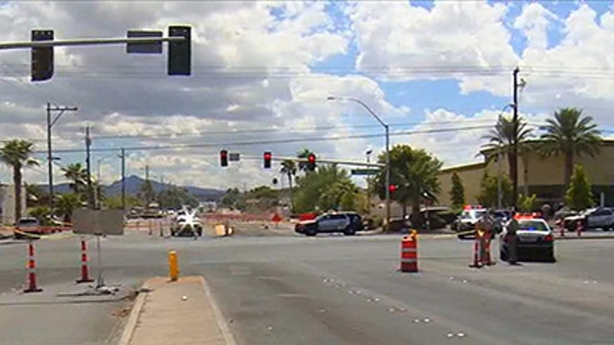 In this image taken from KTNV video, police officers stand guard near the scene where a police officer was shot while stopped at a traffic light in Las Vegas, NV. Sunday, Sept. 6, 2015. Metro Police Sgt. John Sheahan told the Las Vegas Sun that two officers were on their way to respond to a call about a disturbance at a store Sunday afternoon when a man approached on foot and fired a weapon several times at their car, hitting one of the officers. The uninjured policeman pursued the suspect and caught him. (KTNV via AP) LAS VEGAS OUT, MANDATORY CREDIT