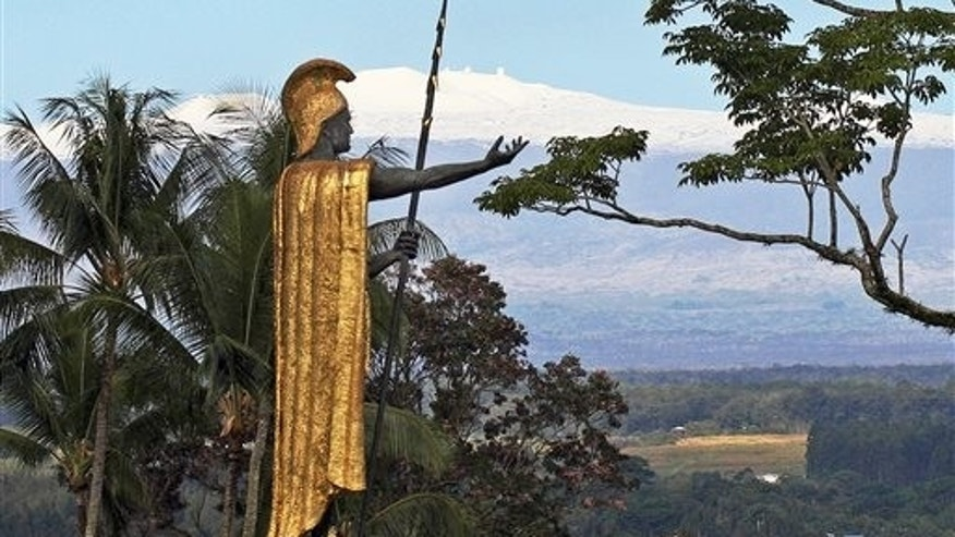 This Jan. 31, 2014, file photo, shows a statue of Hawaiian King Kamehameha I with snow-capped Mauna Kea in the distance, in Hilo, Hawaii. Part of Kamehameha's spear is missing.