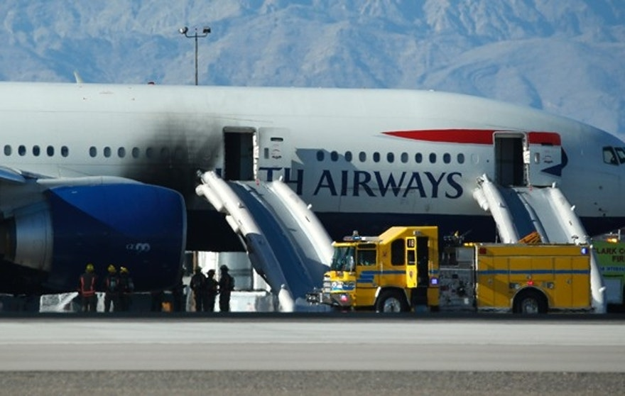 Sept. 8, 2015: Firefighters stand by a plane that caught fire at McCarren International Airport in Las Vegas.