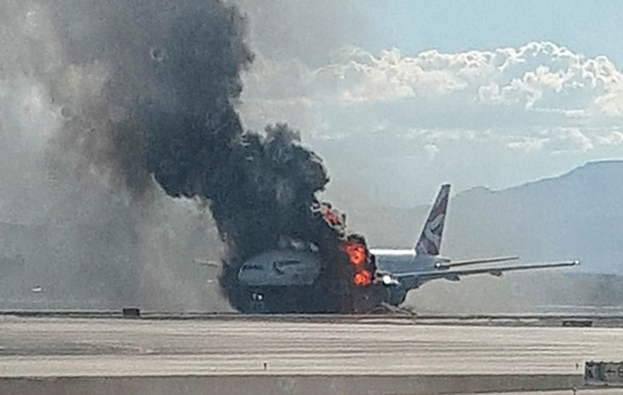 Sept. 8, 2015: In this photo taken from the view of a plane window, smoke billows out from a plane that caught fire at McCarren International Airport in Las Vegas. An engine on the British Airways plane caught fire before takeoff, forcing passengers to escape on emergency slides.