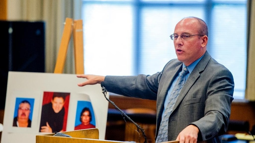 Johnson County District Attorney Steve Howe gives his closing argument near photos of the victims during the penalty phase of the murder trial of Frazier Glenn Miller Jr., Tuesday, Sept. 8, 2015, at the Johnson County Courthouse in Olathe, Kan. Jurors, who convicted the white supremacist on Monday, Aug. 31, of killing three people at Jewish sites in suburban Kansas City in August 2014, are deciding whether to recommend a death sentence. (Allison Long/The Kansas City Star via AP, Pool)