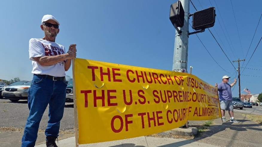 CORRECTS DAY OF WEEK TO TUESDAY INSTEAD OF FRIDAY - Bill Hewitt of Darien, Ga., holds up a sign in support of jailed Rowan County Clerk Kim Davis on the street leading to the the Carter County Detention Center in Grayson, Ky., Tuesday, Sept. 8, 2015. Presidential candidates former Arkansas Gov. Mike Huckabee and Texas Sen. Ted Cruz each planned jailhouse meetings Tuesday with Kentucky clerk Kim Davis, who remains behind bars over her refusal to give marriage licenses to gay couples. (AP Photo/Timothy D. Easley)
