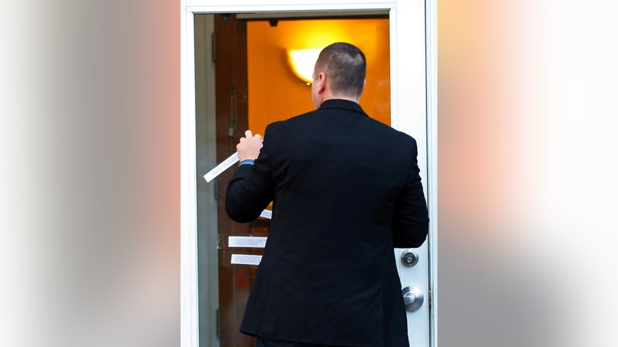 A security guard removes statements pasted to the front door of the dental practice of Walter Palmer, Tuesday, Sept. 8, 2015, in Bloomington, Minn.  Palmer, after weeks out of the public eye, was the subject of an international uproar after he was identified as the hunter who killed the famous lion Cecil in Zimbabwe. (AP Photo/Jim Mone)