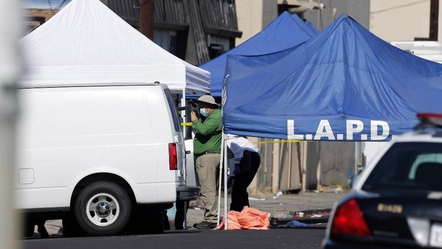 A Los Angeles Police investigator photographs a crime scene, where three children were been found dead inside a car parked outside an elementary school, while a man found with them is in critical condition, Wednesday, Sept. 9, 2015, in South Los Angeles. Officer Jack Richter says the three children were declared dead at the scene while a man found with them was taken to a nearby hospital, also with stab wounds. His relationship to the children wasn't immediately clear. (AP Photo/Nick Ut)