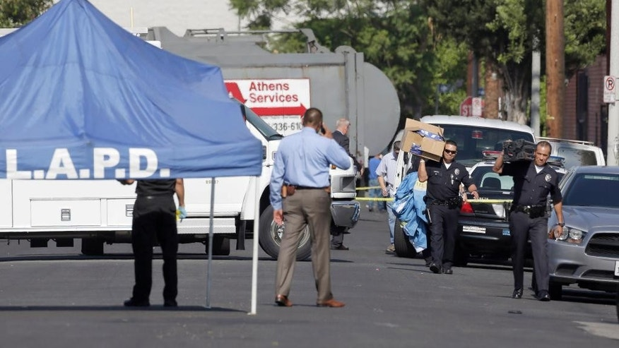 Los Angeles Police Department investigators work at a covered crime scene, where three children were been found dead inside a car parked outside an elementary school, while a man found with them is in critical condition, Wednesday, Sept. 9, 2015, in South Los Angeles. Officer Jack Richter says the three children were declared dead at the scene while a man found with them was taken to a nearby hospital, also with stab wounds. His relationship to the children wasn't immediately clear. (AP Photo/Nick Ut)