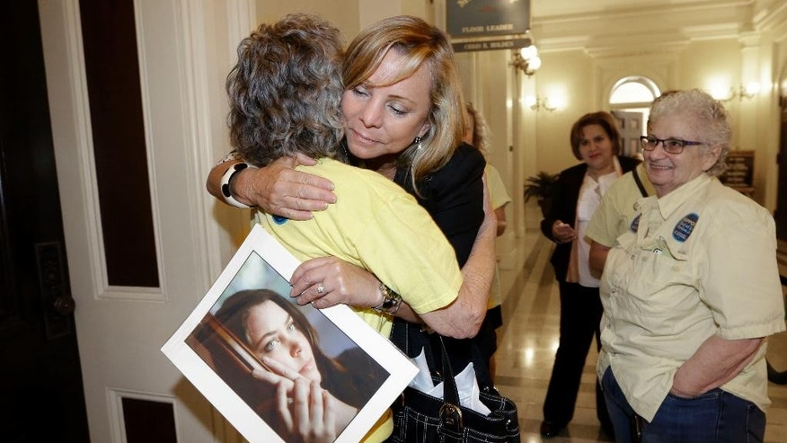 Debbie Ziegler holds a photo of her daughter, Brittany Maynard, as she receives congratulations from Ellen Pontac, after a right-to die measure was approved by the state Assembly, Wednesday, Sept. 9, 2015, in Sacramento, Calif. The bill, approved on a 42-33 vote, that would allow terminally ill patients to legally end their lives, now goes to the Senate.  Brittany Maynard was the California woman with brain cancer who moved to Oregon to legally end her life last fall. (AP Photo/Rich Pedroncelli)