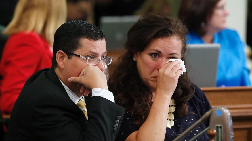 Assemblywoman Lorena Gonzalez, D-San Diego, wipes her eyes as she talks with Assemblyman Rudy Salas, Jr., D-Bakersfield, after her emotion filled speech against a right-to-die measure before the Assembly,  Wednesday, Sept. 9, 2015, in Sacramento, Calif. On a 42-33 vote lawmakers approved the bill, by Assemblywoman Susan Talamantes Eggman, that would allow terminally ill patients to legally end their lives.  It now goes to the Senate.  Salas voted for the bill.(AP Photo/Rich Pedroncelli)