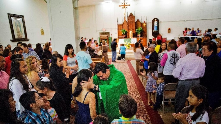 "The Rev. William Canales greets parishioners during Mass at St. John Paul II Pastoral Center in Gainesville, Ga., on Sunday, Aug. 9, 2015. Canales noted the pope's exhortation for priests to be close to the marginalized and be ""shepherds living with the smell of the sheep."" Canales joked, ""I smell like the chicken here."" (AP Photo/David Goldman)"