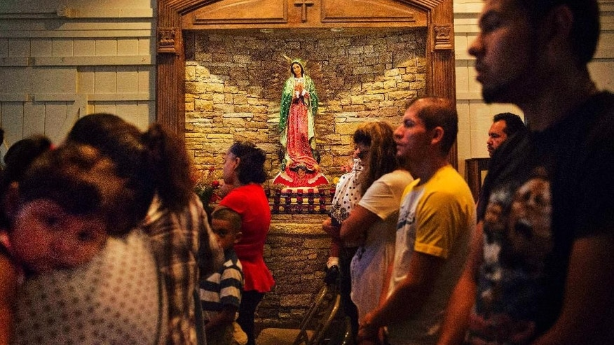 Worshippers pray next to a shrine to Our Lady of Guadalupe, the patroness of the Americas especially revered by Mexicans, during Mass at the St. John Paul II Pastoral Center in Gainesville, Ga., on Sunday, Aug. 9, 2015. The Roman Catholic mission sits at the rough end of a former strip mall in the shadow of an Arby's. The space, church leaders say, was once used as a nightclub and movie theater, a history now hidden by multiple coats of paint, pews brought in from other congregations, and a stone-and-wood shrine to Our Lady of Guadalupe. (AP Photo/David Goldman)