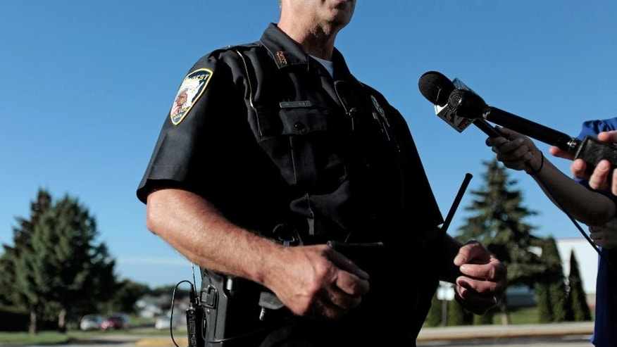 DeForest police chief Robert Henze talks with reporters outside Yahara Elementary School in DeForest, Wis., Wednesday, Sept. 9, 2015. A Wisconsin school district says police have found nothing as they search an elementary school where someone reported a man with a gun. (Michael P. King/Wisconsin State Journal via AP) MANDATORY CREDIT