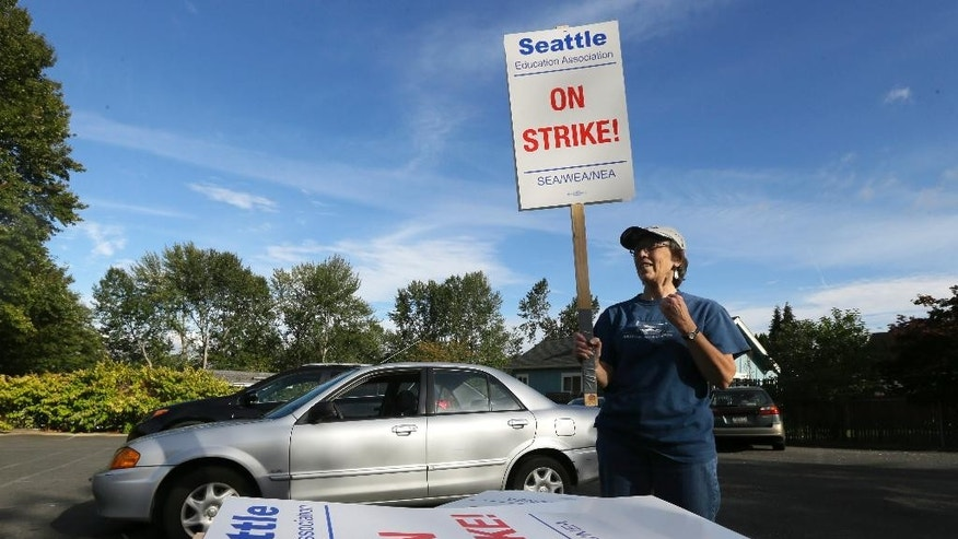 Nancy Kiser, a fifth-grade teacher at Kimball Elementary School, examines a picket sign to be used in the event of a strike by teachers in the Seattle School District, Tuesday, Sept. 8, 2015, in Seattle. Seattle teachers voted overwhelmingly last week to strike if the district and teachers fail to reach a contract agreement by the first day of school on Wednesday. (AP Photo/Ted S. Warren)