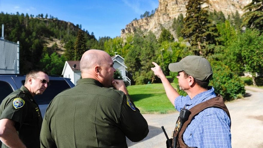 Deputy Uriah Wood, right, speaking with members of the Montana Highway Patrol, points to the mountainous slope the missing murder supect allegedly scaled Monday morning after ditching a vehicle at Hauser Dam near Helena, Mont., Tuesday morning, Sept. 8, 2015, as teams of officers swept door to door looking for Branden Conrad Miesmer, 26, suspected of shooting and killing a man in Great Falls, Mont., sometime Sunday night or early Monday, Sept. 7, 2015. Police said he then forced two people to drive him to Helena. Police believe Miesmer is wandering armed and barefoot and possibly cold and hungry in the hills north of Helena. They were searching Tuesday, Sept.. 8, 2015, near Hauser Dam to the suspect, said Lewis and Clark County Sheriff Leo Dutton. (Thom Bridge/Independent Record via AP) MANDATORY CREDIT